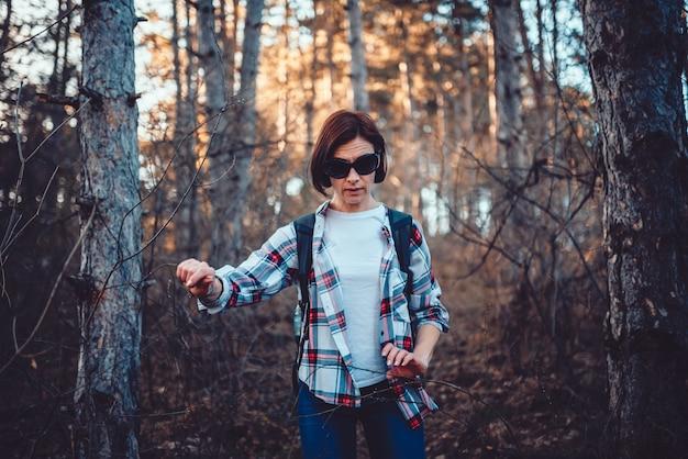 Donna che cammina attraverso la fitta foresta