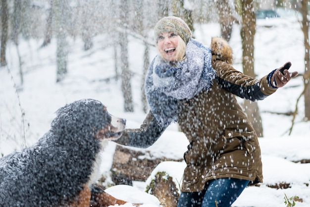 Donna che cammina con il suo cane in inverno ed entrambi esplorano la neve