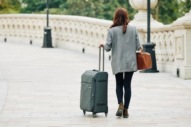 Donna che cammina con la grande valigia