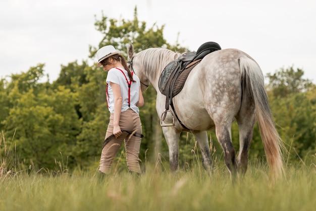 Donna che cammina con un cavallo in campagna