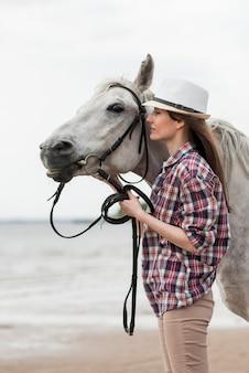Donna che cammina con un cavallo sulla spiaggia