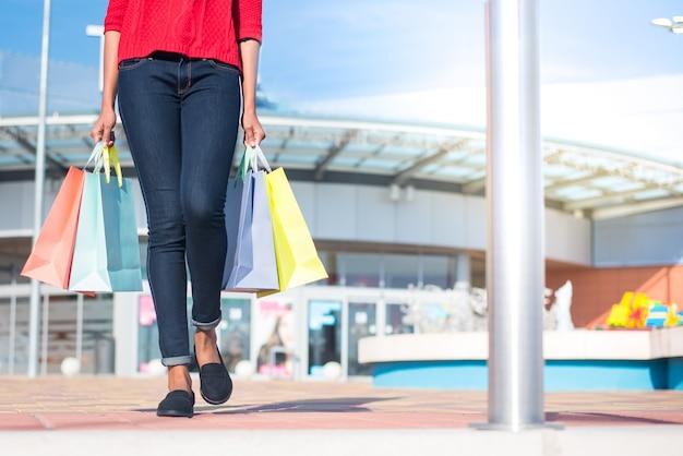 Donna che cammina fuori da un centro commerciale con sacchetti colorati