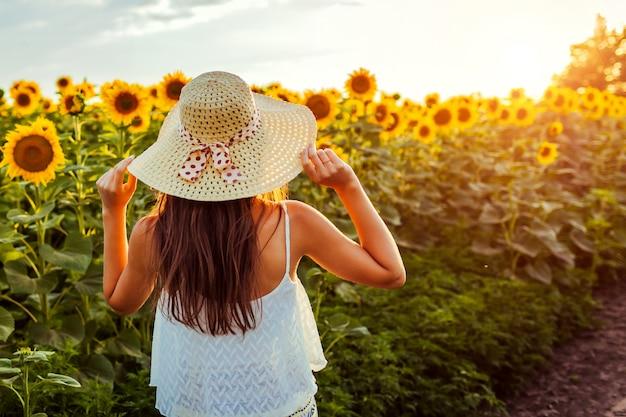 Donna che cammina in cappello di paglia di fioritura della tenuta del giacimento del girasole. vacanze estive