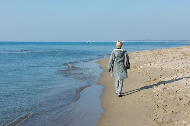 Donna che cammina in riva al mare in inverno