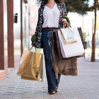 Donna che cammina in strada con borse della spesa
