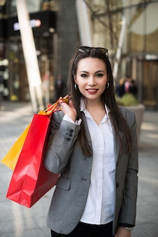 Donna che cammina in una strada cittadina con borse della spesa
