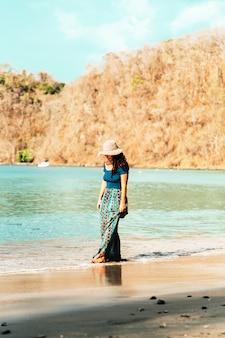 Donna che cammina lungo la riva del mare