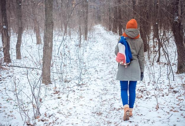 Donna che cammina nel bosco invernale.