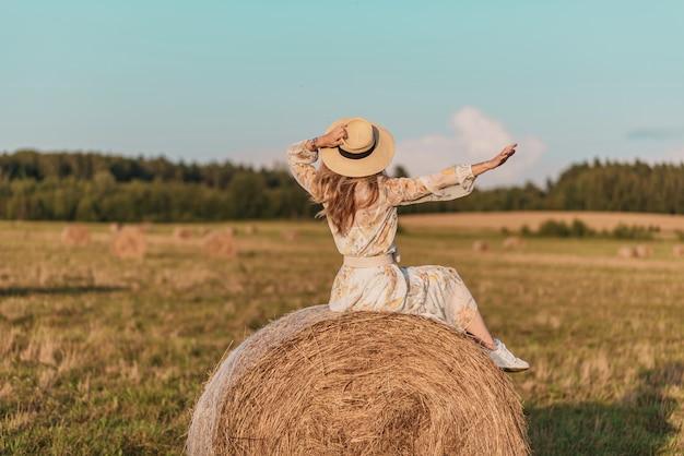 Donna che cammina nel campo con covoni di fieno