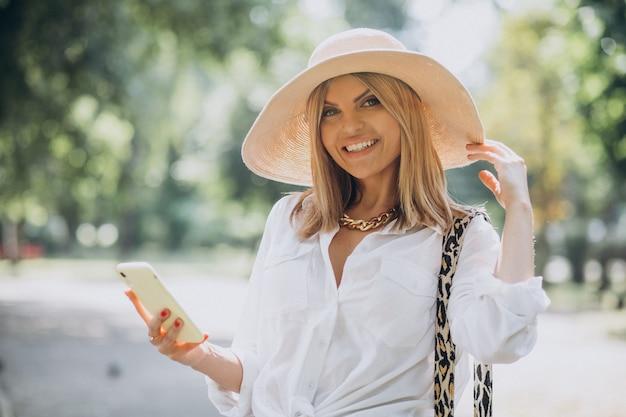 Donna che cammina nel parco e parla al telefono