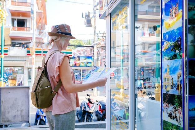 Donna che cammina per le strade della città con una mappa, godendo il viaggio. ufficio dell'agenzia di viaggi e tour di scelta turistica.
