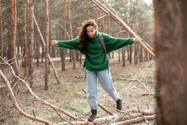 Donna che cammina sull'albero caduto