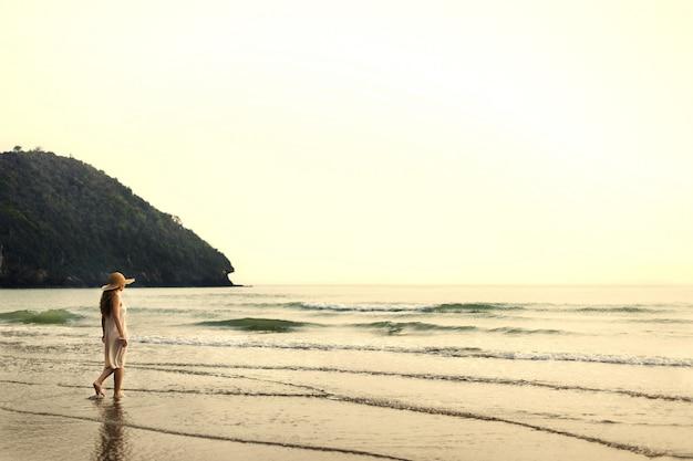 Donna che cammina sulla riva