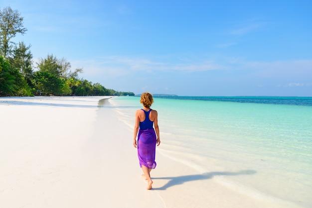 Donna che cammina sulla spiaggia tropicale. gente reale del mar dei caraibi dell'acqua trasparente del turchese della spiaggia di sabbia bianca di retrovisione. indonesia kei islands moluccas destinazione.