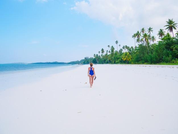 Donna che cammina sulla spiaggia tropicale. gente reale del mar dei caraibi dell'acqua trasparente del turchese della spiaggia di sabbia bianca di retrovisione. indonesia