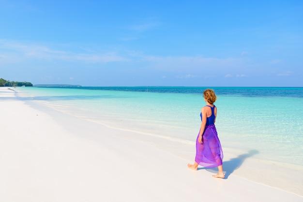 Donna che cammina sulla spiaggia tropicale. gente reale del mar dei caraibi dell'acqua trasparente del turchese della spiaggia di sabbia bianca di retrovisione