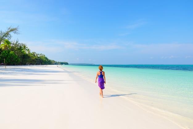 Donna che cammina sulla spiaggia tropicale