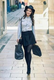 Donna che cammina sulla strada con borse della spesa