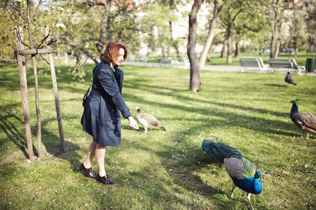 Donna che cammina tra i pavoni in un parco pubblico a praga