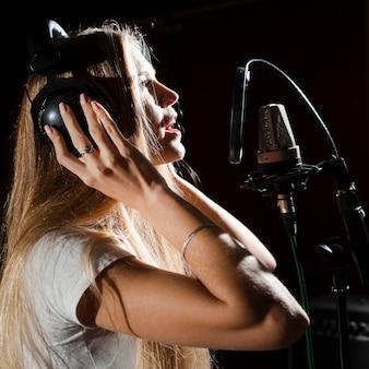 Donna che canta nel microfono e che indossa le cuffie