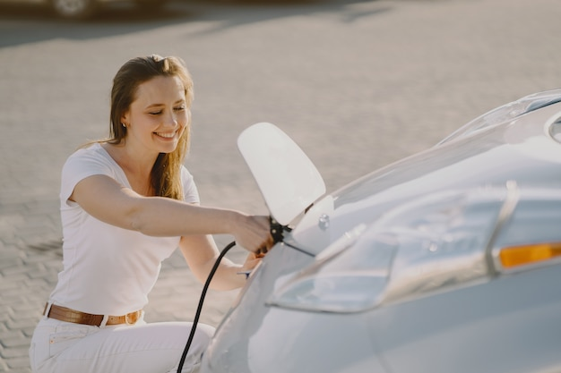 Donna che carica elettro automobile alla stazione di servizio elettrica