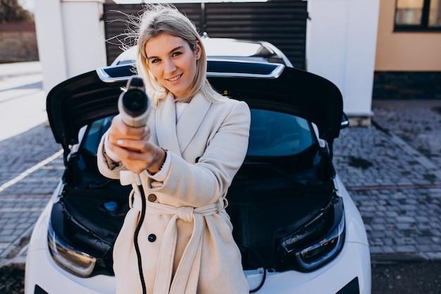 Donna che carica elettro automobile da casa sua e che tiene caricatore