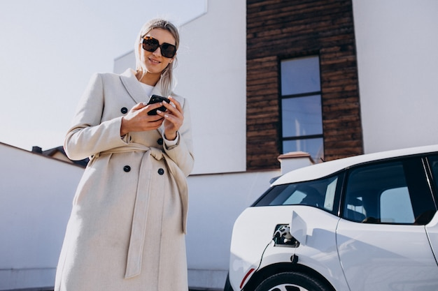 Donna che carica elettro automobile e che per mezzo del telefono