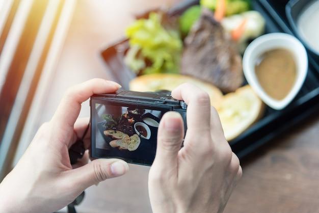 Donna che cattura foto di cibo sulla fotocamera al ristorante con tavolo in legno rustico.
