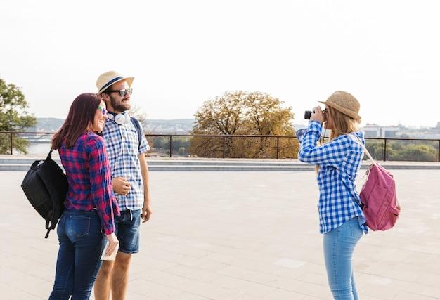 Donna che cattura foto di felice giovane coppia sulla fotocamera