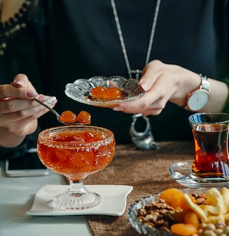 Donna che cattura la marmellata di amarene dalla ciotola di cristallo, bevendo tè nero