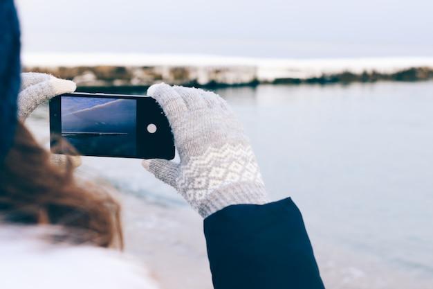 Donna che cattura le immagini della spiaggia su un telefono mobile in inverno