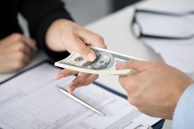 Donna che cattura lotto di banconote da cento dollari. le mani si chiudono