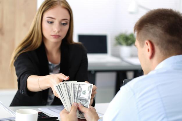 Donna che cattura lotto di banconote da cento dollari. venalità, tangente, concetto di corruzione