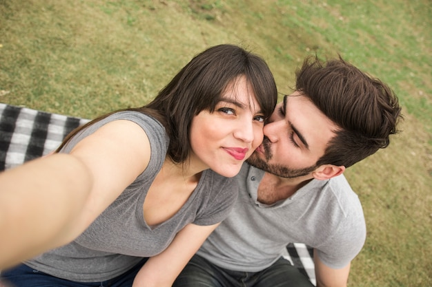 Donna che cattura selfie mentre il suo ragazzo si bacia