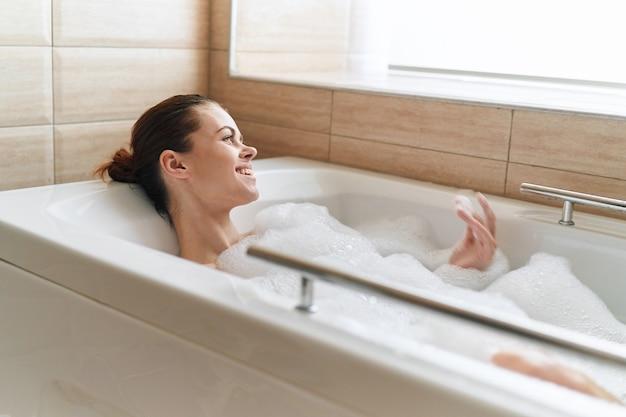 Donna che cattura un bagno di bolle a casa