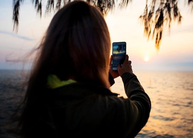 Donna che cattura una foto al tramonto sulla fotocamera del telefono