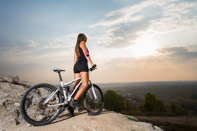 Donna che cavalca sulla bicicletta sportiva sulla collina di montagna