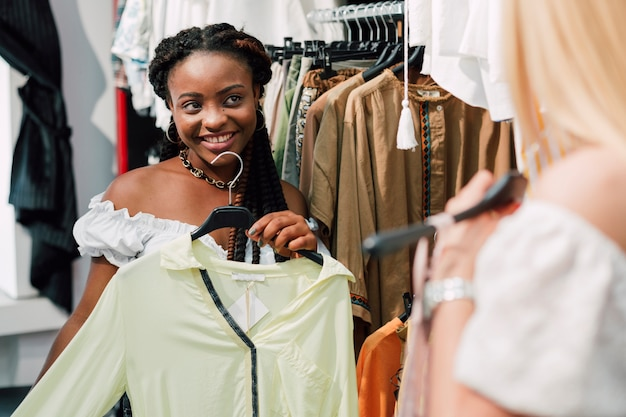 Donna che chiede alla sua amica opinione sui vestiti