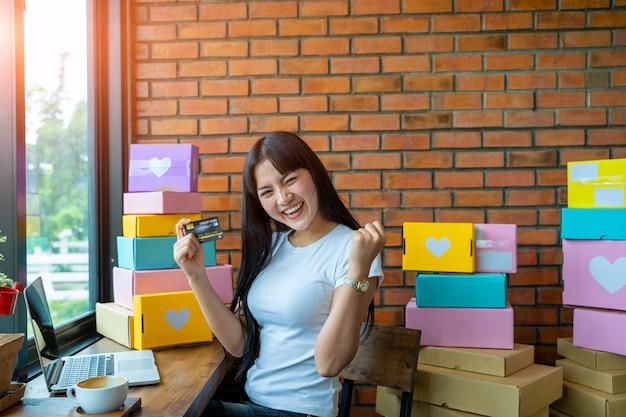 Donna che compera online con uno smartphone, le giovani donne sono felici di acquistare online con carta di credito e un computer portatile seduto in salotto a casa.