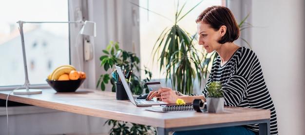 Donna che compera online e che usando la carta di credito