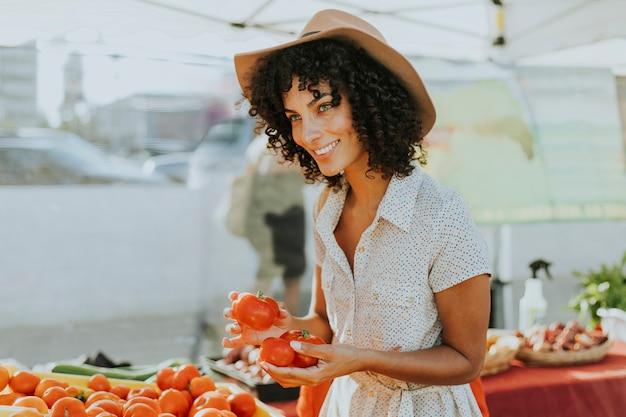 Donna che compra i pomodori in un mercato degli agricoltori