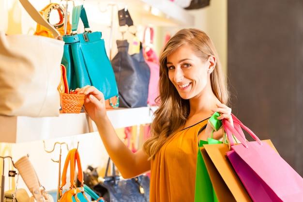 Donna che compra una borsa in centro commerciale