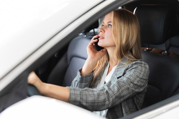 Donna che comunica sul telefono in auto