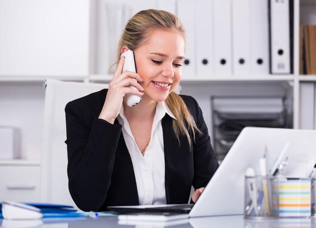 Donna che comunica sul telefono in ufficio