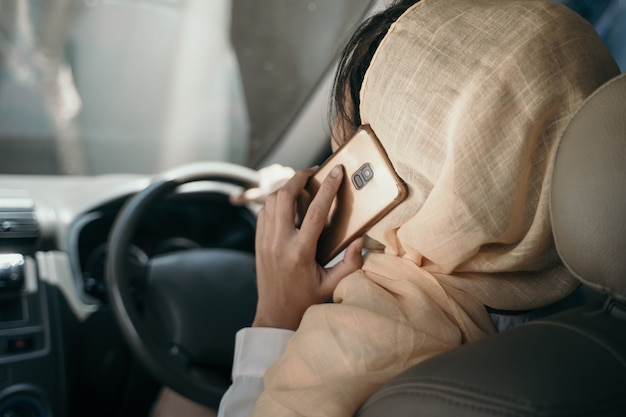Donna che conduce automobile mentre avendo telefonata