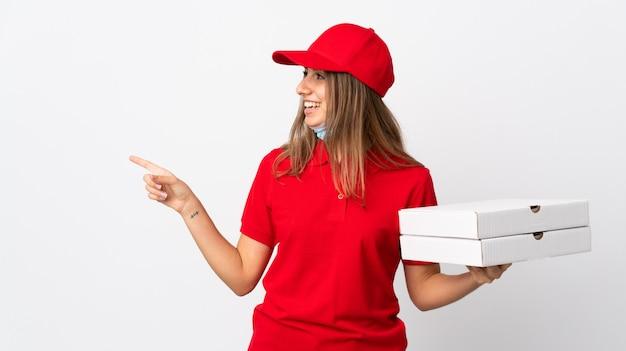Donna che consegna una pizza tenendo una pizza e proteggendo dal coronavirus con una maschera sul muro bianco isolato che punta verso il lato per presentare un prodotto