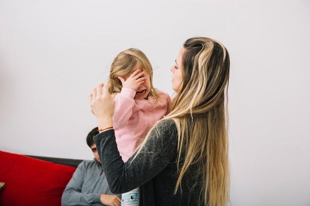 Donna che consola la sua piccola figlia piangente