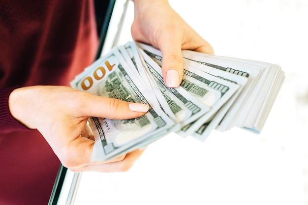 Donna che conta le banconote dei soldi. foto di concetto di tassi di cambio del denaro, di attività bancarie, di valuta e di valuta estera
