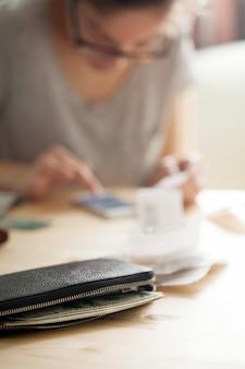 Donna che conta soldi sul suo telefono