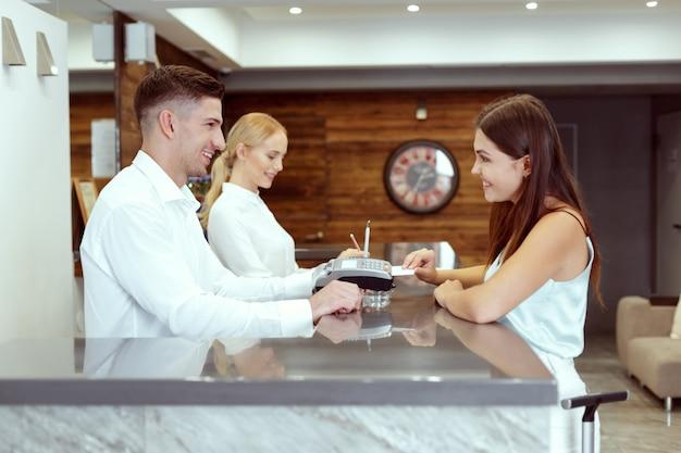 Donna che controlla alla reception dell'hotel